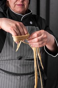 Vista frontale del cuoco unico femminile che produce tagliatelle