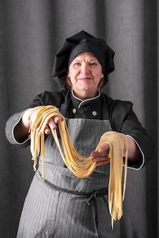 Vista frontale del cuoco unico femminile che tiene pasta fresca