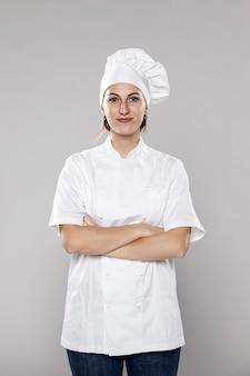 Vista frontale del cuoco unico femminile con le braccia attraversate