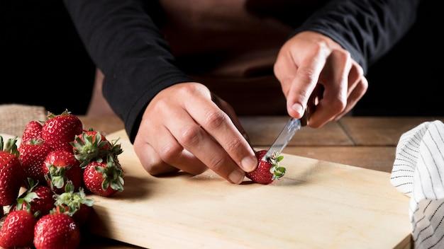Vista frontale del cuoco unico in grembiule che taglia le fragole a pezzi