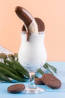 Vista frontale del dessert in vetro con cioccolato e biscotti alla banana