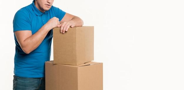 Vista frontale del fattorino e scatole di cartone