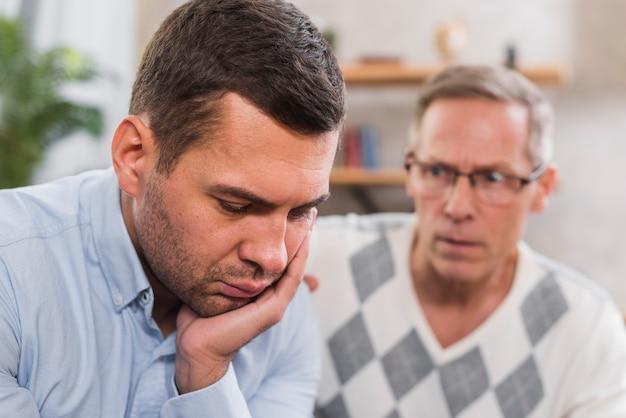 Vista frontale del figlio triste e suo padre