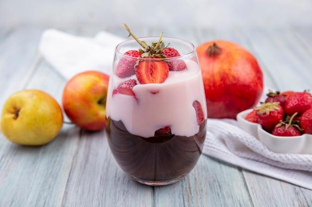 Vista frontale del frappè con fragola e cioccolato con mele e melograno su superficie grigia