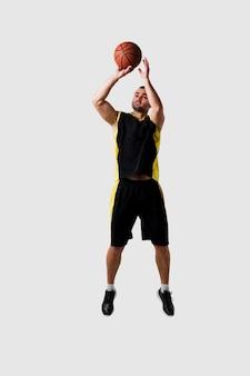 Vista frontale del giocatore di pallacanestro che posa a mezz'aria mentre gettando palla
