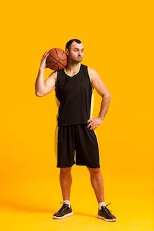 Vista frontale del giocatore di pallacanestro maschio che posa con la palla sulla spalla