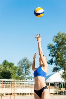 Vista frontale del giocatore di pallavolo femminile sulla spiaggia che serve palla