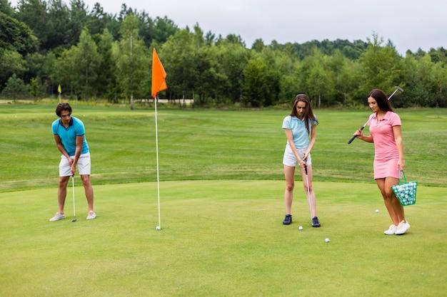 Vista frontale del gioco giovane golfisti