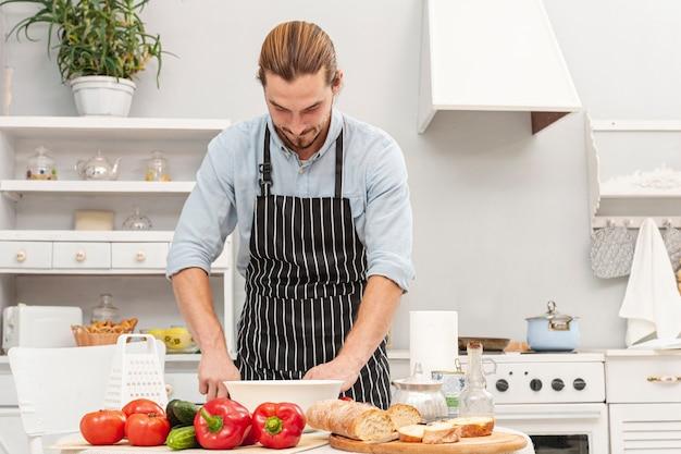 Vista frontale del giovane bello cucinare