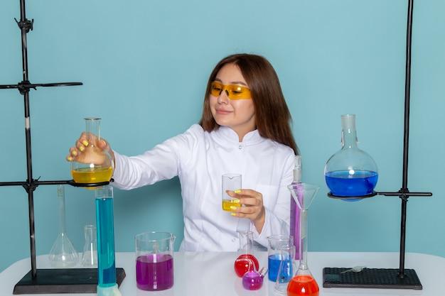 Vista frontale del giovane chimico feman in abito bianco davanti al tavolo di lavoro con soluzioni sulla superficie blu