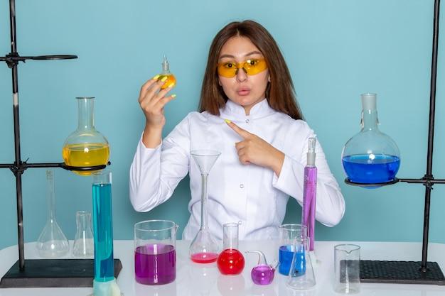 Vista frontale del giovane chimico feman in abito bianco davanti al tavolo di lavoro con soluzioni