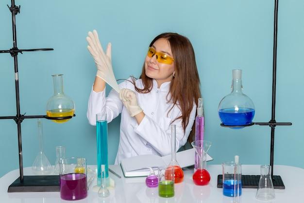 Vista frontale del giovane chimico femmina in abito bianco davanti al tavolo di lavoro con soluzioni e indossando guanti