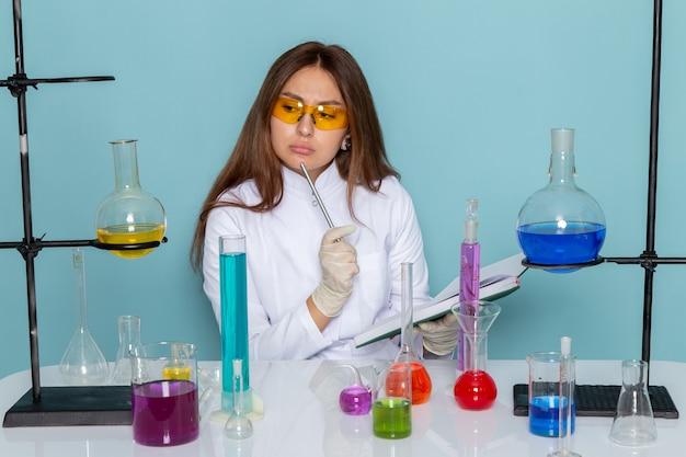 Vista frontale del giovane chimico femmina in abito bianco davanti al tavolo di lavoro con soluzioni e scrivere le note