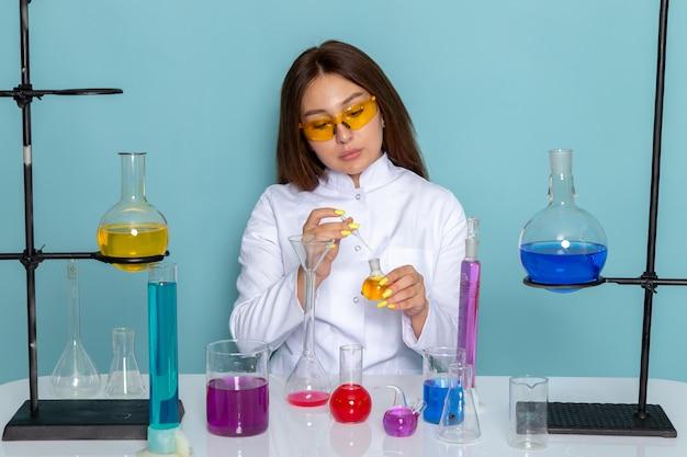 Vista frontale del giovane chimico femmina in abito bianco davanti al tavolo di lavoro con soluzioni sui prodotti chimici di superficie blu