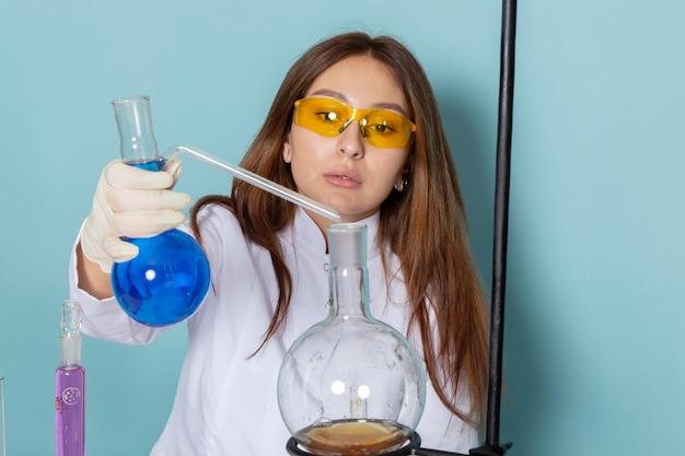 Vista frontale del giovane chimico femmina in abito bianco davanti al tavolo di lavoro con soluzioni