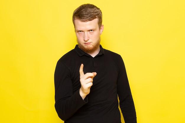Vista frontale del giovane in camicia nera che posa con il segnale di pericolo