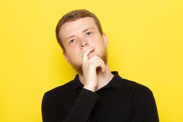 Vista frontale del giovane in camicia nera che posa con l'espressione di pensiero