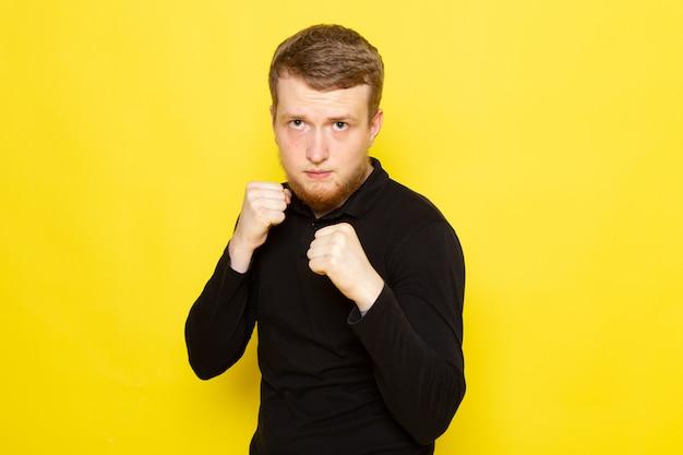 Vista frontale del giovane in camicia nera che posa con la posa di pugilato