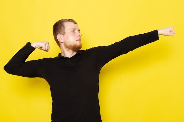 Vista frontale del giovane nella posa nera della camicia