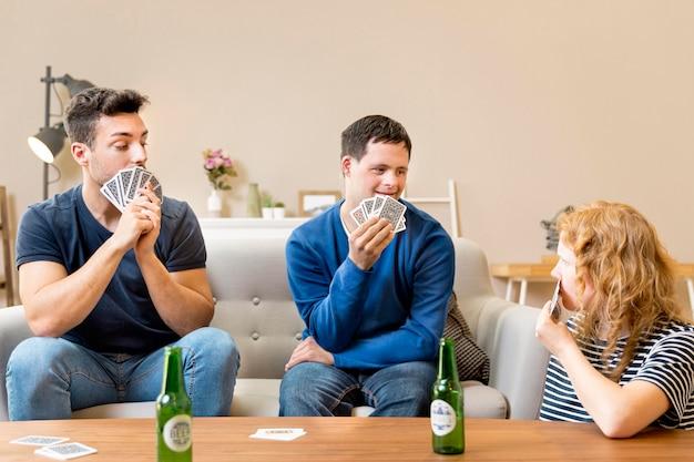Vista frontale del gruppo di amici che giocano a carte a casa e che mangiano birra