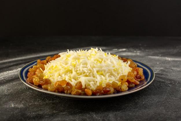 Vista frontale del gustoso pilaf con olio e uvetta secca all'interno del piatto sulla superficie scura