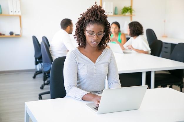 Vista frontale del lavoratore attraente messo a fuoco che scrive sul computer portatile