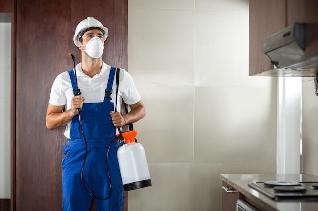 Vista frontale del lavoratore dei parassiti che spruzza nella cucina