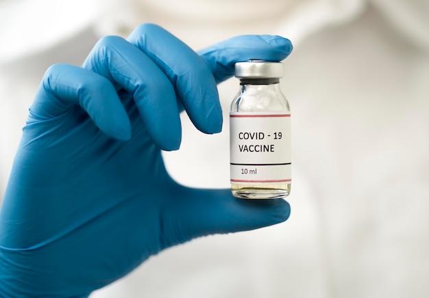 Vista frontale del medico che tiene il vaccino contro il coronavirus
