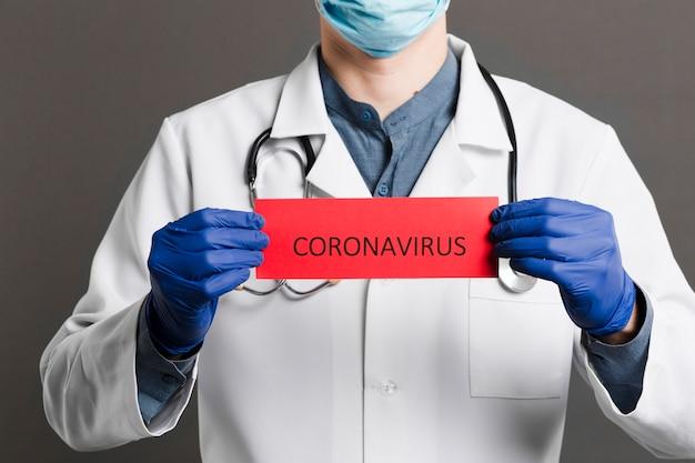 Vista frontale del medico con stetoscopio in possesso di carta con coronavirus