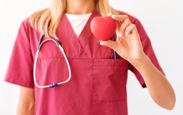 Vista frontale del medico femminile che tiene a forma di cuore
