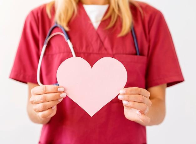 Vista frontale del medico femminile con lo stetoscopio che tiene il cuore di carta