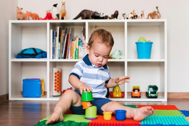 Vista frontale del neonato sveglio felice che gioca con i giocattoli