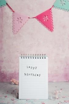 Vista frontale del notebook con auguri e ghirlanda di buon compleanno