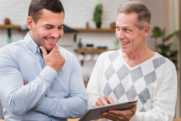 Vista frontale del padre che mostra a suo figlio il tablet