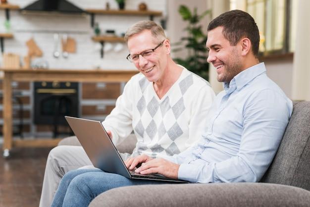 Vista frontale del padre e del figlio che esaminano computer portatile