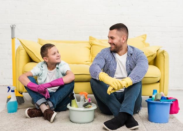 Vista frontale del padre e del figlio che riposano accanto ai prodotti per la pulizia