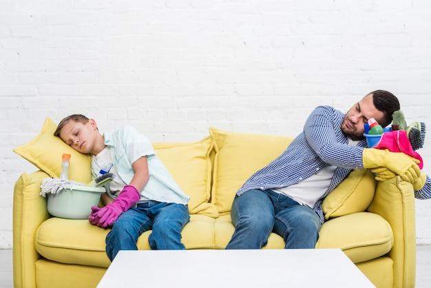 Vista frontale del padre e del figlio che riposano sul sofà dopo la pulizia