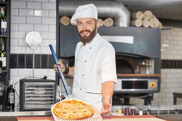 Vista frontale del panettiere che indossa la tunica dello chef e mantenendo la pizza sulla pala metallica.