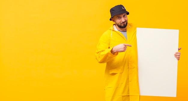 Vista frontale del pescatore che indica al cartello in bianco con lo spazio della copia