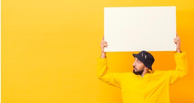 Vista frontale del pescatore che tiene cartello in bianco con lo spazio della copia