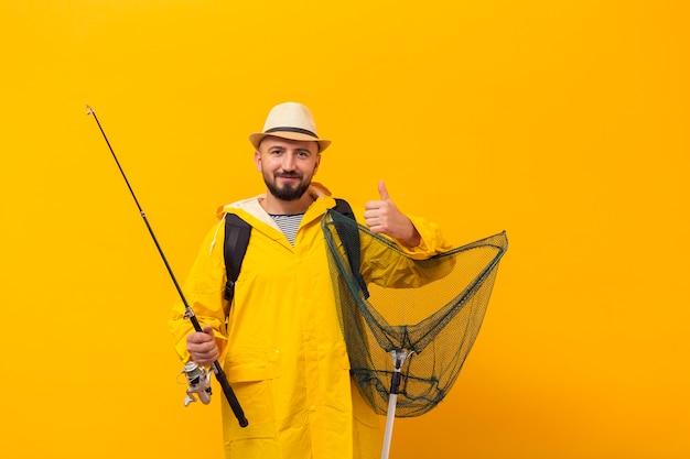 Vista frontale del pescatore che tiene rete e che dà i pollici in su