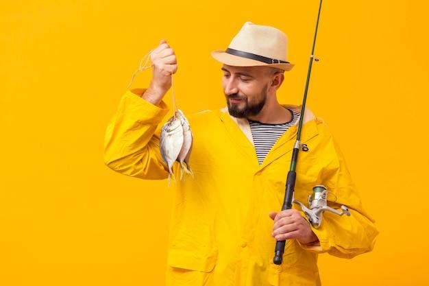 Vista frontale del pescatore fiero che tiene fermo e canna da pesca