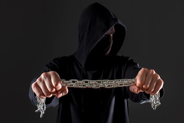 Vista frontale del pirata informatico maschio che tiene catena del metallo