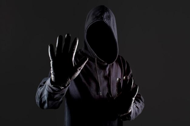 Vista frontale del pirata informatico maschio con i guanti che tengono mano su come fermata