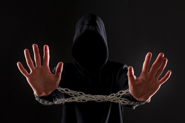 Vista frontale del pirata informatico maschio con la catena del metallo intorno alle mani