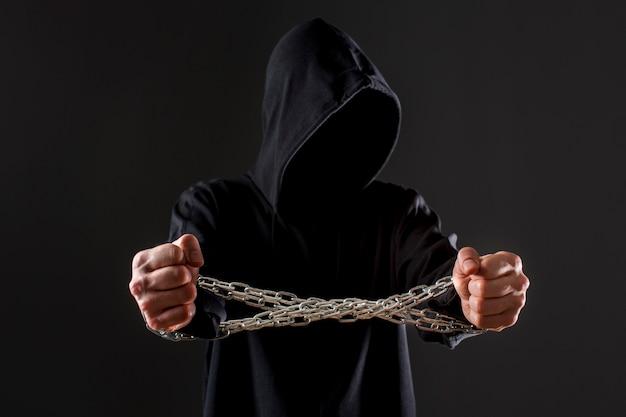 Vista frontale del pirata informatico maschio con le mani legate dalla catena del metallo