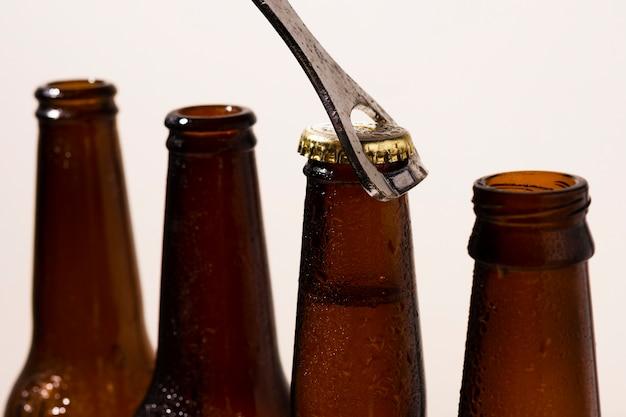 Vista frontale del processo di apertura delle bottiglie di birra