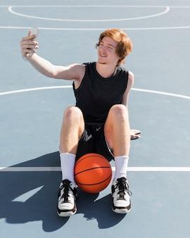 Vista frontale del ragazzo che prende un selfie