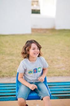 Vista frontale del ragazzo che si siede nella sedia