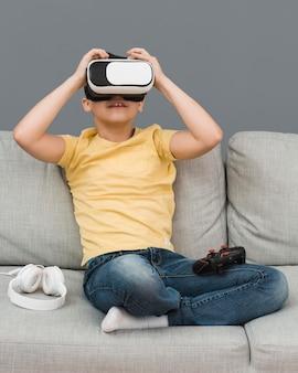 Vista frontale del ragazzo che usando le cuffie da realtà virtuale